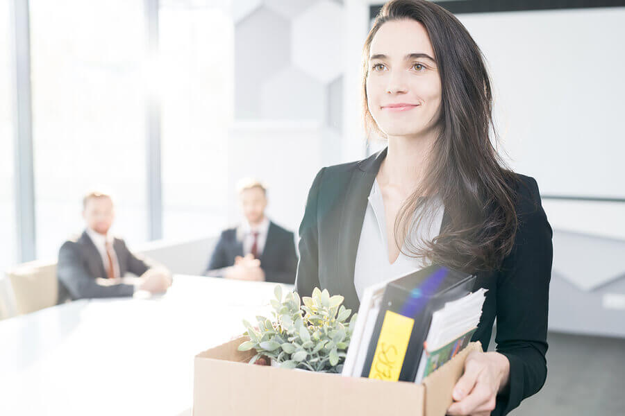 smiling woman carrying box of belongings leaves her employer